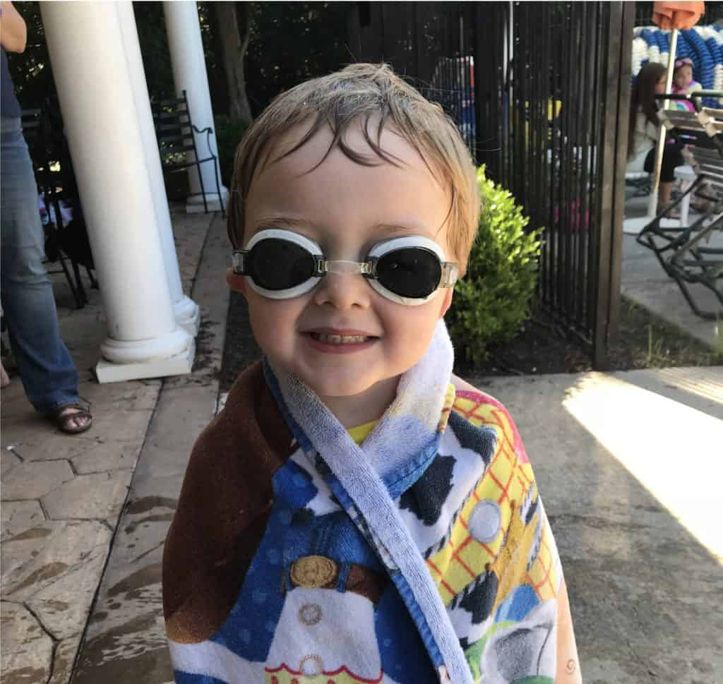 Image of boy in towel and goggles at pool for summer survival