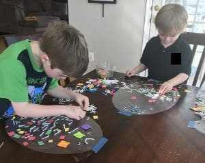Toddler and Preschooler working on their Easter craft on a table