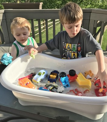 Toddler and Preschooler washing trucks for an outside summer activity