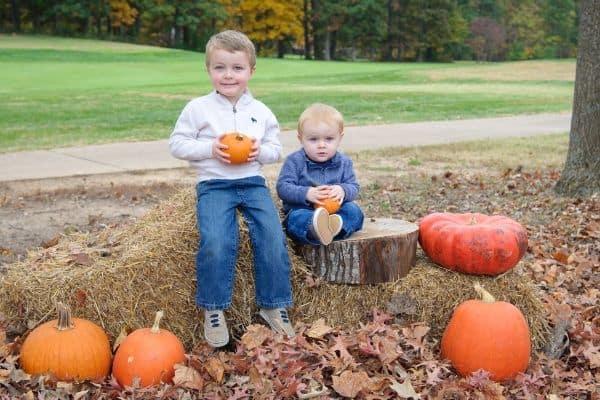 boys on a fall scavenger hunt holding pumpkins