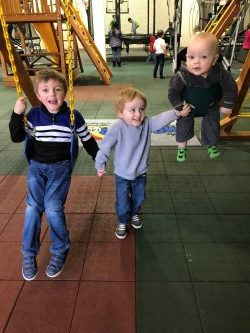 3 kids playing at a playplace with passes they received as a gift idea for christmas