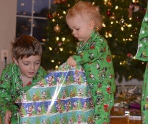 two boys opening a christmas gifts that aren't toys