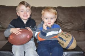 two kids with two footballs they received as christmas gifts