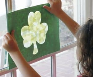 little girl hanging up her st. patrick's day shamrock craft