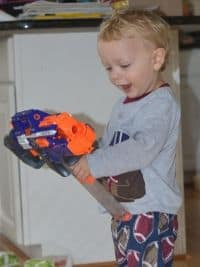 toddler playing with a nerf gun