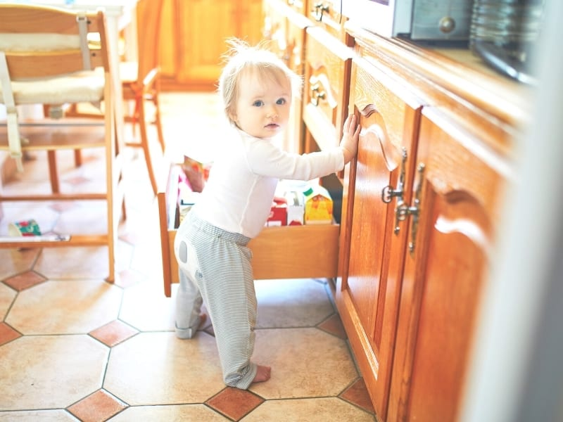 Childproofing and toddler proofing your home featured image of a toddler opening a cabinet
