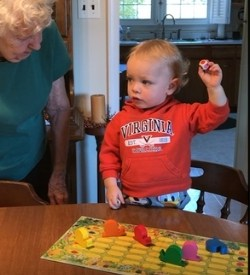 3 year old playing the best board game snail game with grandmother