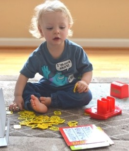 2 or 3 year old boy playing a Zingo board game