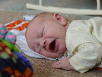one month old baby crying during tummy time activities