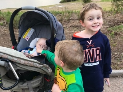 a toddler, preschooler, and a 1 month old baby on a walk