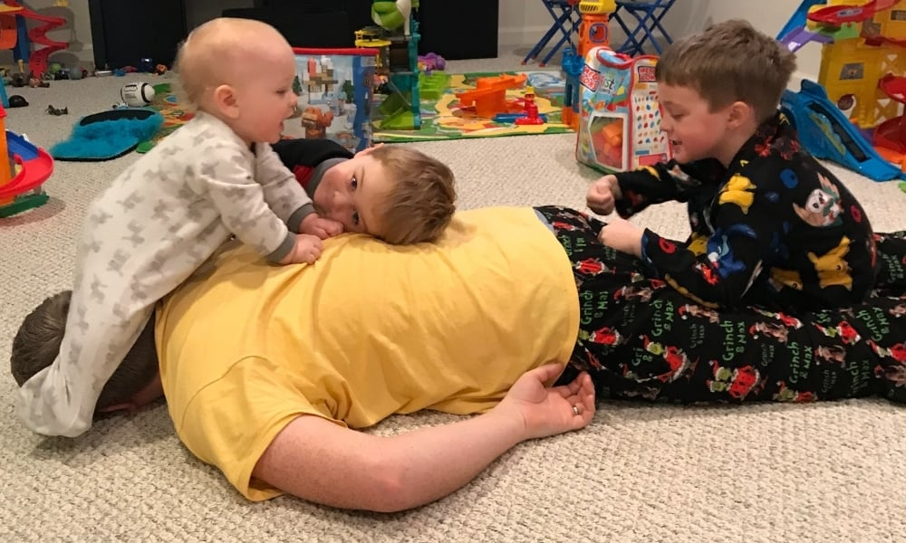 the most difficult thing about parenting featured image with three boys tackling dad