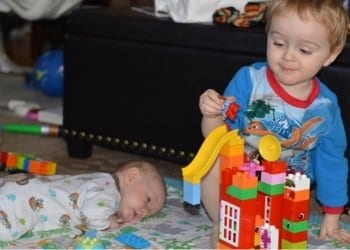 a big brother helping his baby brother do tummy time