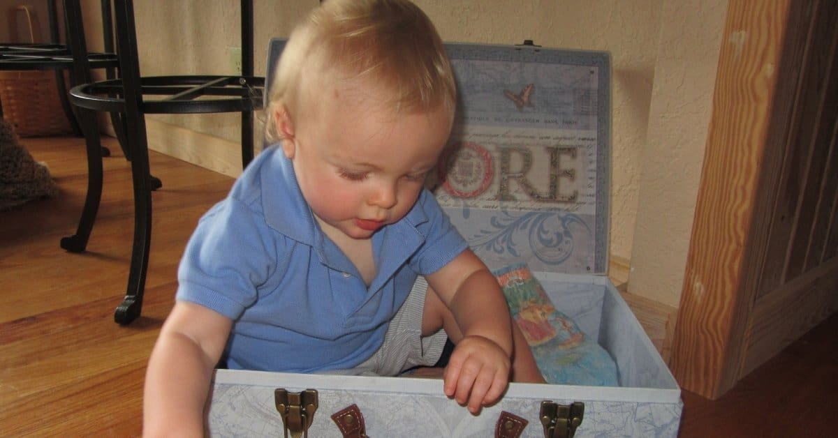 best toddler activities featured image of a toddler in a box
