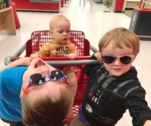 toddler preschooler and baby in a shopping cart